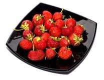 在一个大黑色的盘子的成熟草莓 免版税库存照片