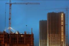 在一个大建造场所的起重机,未完成的多层的房子,有雾的晚上微明 免版税图库摄影
