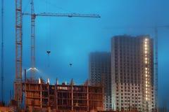 在一个大建造场所的起重机,未完成的房子,雾盖顶层,平衡微明 免版税库存图片