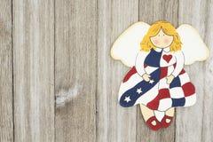 在一个天使的美国爱国老旗子在一被风化的木backgroun 免版税库存照片