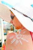 在一个女孩的肩膀的太阳绘了遮光剂 库存图片