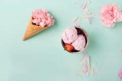 在一个奶蛋烘饼锥体的冰淇凌在绿松石背景 背景奶油色冰查出的草莓白色 在奶蛋烘饼锥体的花 桃红色康乃馨 免版税库存照片