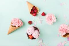 在一个奶蛋烘饼锥体的冰淇凌在绿松石背景 背景奶油色冰查出的草莓白色 在奶蛋烘饼锥体的花 桃红色康乃馨 库存图片