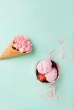 在一个奶蛋烘饼锥体的冰淇凌在绿松石背景 背景奶油色冰查出的草莓白色 在奶蛋烘饼锥体的花 桃红色康乃馨 免版税库存图片