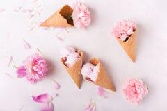 在一个奶蛋烘饼锥体的冰淇凌在轻的背景 背景奶油色冰查出的草莓白色 在奶蛋烘饼锥体的花 桃红色康乃馨 在wo的花 免版税库存图片