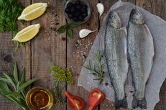 在一个委员会的两条河鳟鱼,用草本,香料、柠檬和胡椒在木板,为烹调准备 新鲜的鱼 免版税图库摄影