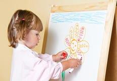 在一个委员会的小女孩油漆有标志的 库存照片