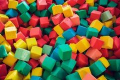 在一个孩子的水池的许多五颜六色的软的块在操场 明亮的多彩多姿的软的立方体,几何玩具 r 免版税库存照片