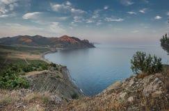 在一个安静的海湾的微明在山的脚 图库摄影