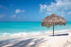 在一个完善的白色海滩的沙滩伞在海前面 免版税库存图片