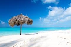 在一个完善的白色海滩的沙滩伞在海前面 库存图片