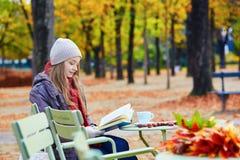 读在一个室外咖啡馆的女孩一本书 免版税库存照片