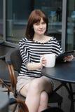 在一个室外咖啡馆的女孩饮用的咖啡 免版税库存照片