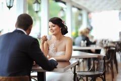 在一个室外咖啡馆的新愉快的新娘和新郎 免版税库存图片