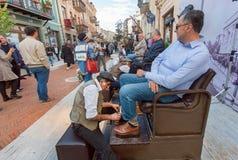 在一个室外节日期间,鞋子擦净剂摩擦在街道上的客户鞋子 免版税库存图片
