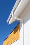 在一个家的新的雨天沟有反对蓝天的木盘区的 免版税库存图片