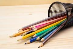 在一个容器的五颜六色的铅笔在木表 库存图片