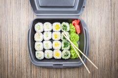 在一个容器的寿司卷在一张木桌上 顶视图 免版税库存图片