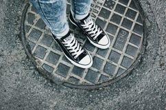 在一个对的少年脚黑帆布鞋 免版税库存照片