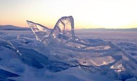 在一个小丘领域的透明冰川在日落的冻西伯利亚人贝加尔湖在冬天 库存照片