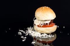 在一个小圆面包的丸子用蕃茄蛋黄酱和搓碎干酪在黑背景 库存照片