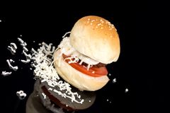 在一个小圆面包的丸子用蕃茄蛋黄酱和搓碎干酪在黑背景 库存图片