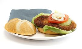 在一个小圆面包的维也纳炸小牛排用莴苣蕃茄和蛋黄酱 免版税库存照片