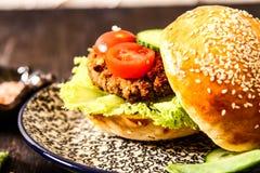 在一个小圆面包的自创素食者汉堡用芝麻 免版税库存照片