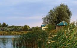 在一个小小河或池塘的边缘的附近木客舱在临近日落的茂盛植物中 免版税库存照片
