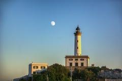 在一个小山顶的灯塔日落的 库存照片