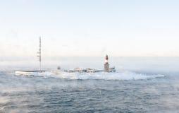 在一个小岛的灯塔在有薄雾的海 库存照片