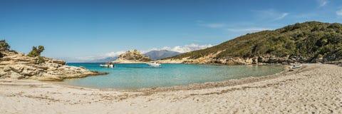 在一个小岩石小海湾的小船与沙滩在可西嘉岛 免版税库存照片