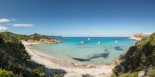 在一个小岩石小海湾的小船与沙滩在可西嘉岛 库存图片