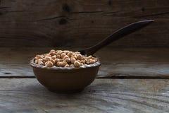 在一个小棕色碗的鸡豆有在黑暗的土气wo的一把匙子的 免版税库存图片
