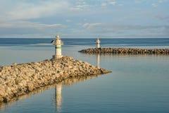 在一个小港口的入口的两座小跳船灯塔 免版税库存图片