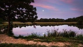 在一个小湖或池塘反映的满月在日出 图库摄影