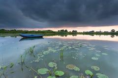 在一个小湖的划艇在多云日落期间 库存照片