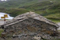 在一个小湖的岸的老石瑞士山中的牧人小屋高山山的 grindelwald瑞士 免版税库存照片