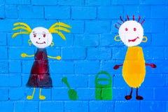 在一个小男孩和女孩,原始的墙壁上的图片 免版税库存照片