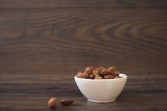 在一个小白色碗的焦糖的杏仁在木背景 免版税库存图片