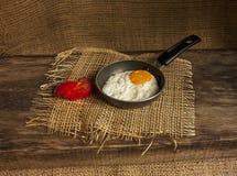 在一个小的煎锅的煎蛋在委员会 库存图片