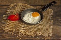 在一个小的煎锅的煎蛋在委员会 免版税库存图片