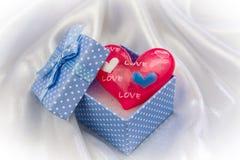在一个小的蓝色礼物盒的红色爱心脏 库存图片