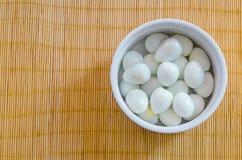 在一个小碗的煮沸的鹌鹑蛋在一张竹席子 免版税库存照片