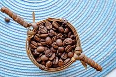 在一个小篮子的咖啡豆使上面环境美化 免版税图库摄影