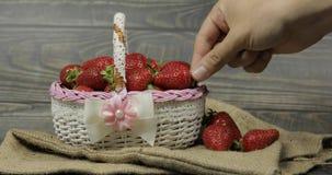 在一个小篮子的草莓在木桌上 人的手采取莓果 免版税图库摄影