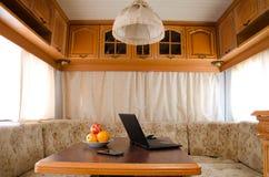 在一个小舒适厨房里打开有果子盛肉盘和一个智能手机的笔记本在一张桌上 免版税库存照片