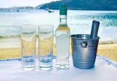 在一个小酒馆的希腊ouzo在海前面 免版税库存照片