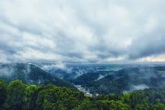 在一个小镇的美丽的景色与剧烈的多云天空的山的 库存照片