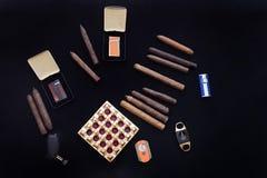 在一个小组在黑色和灰盘的滚动的雪茄有切削刀的 库存图片